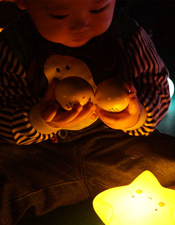 Toddler playing with light up toys in the dark