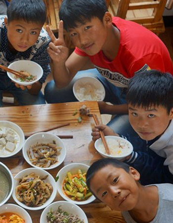 Children eating food at a table together