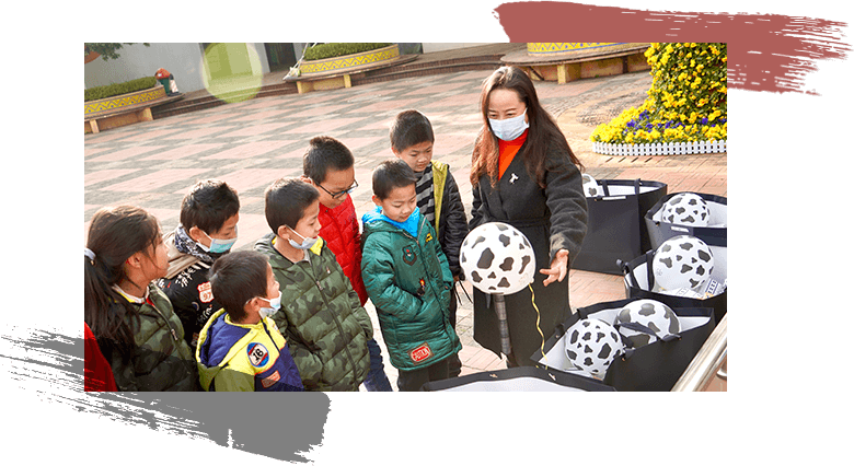 A group of children, all ages, receiving goodie bags of fun and useful items.