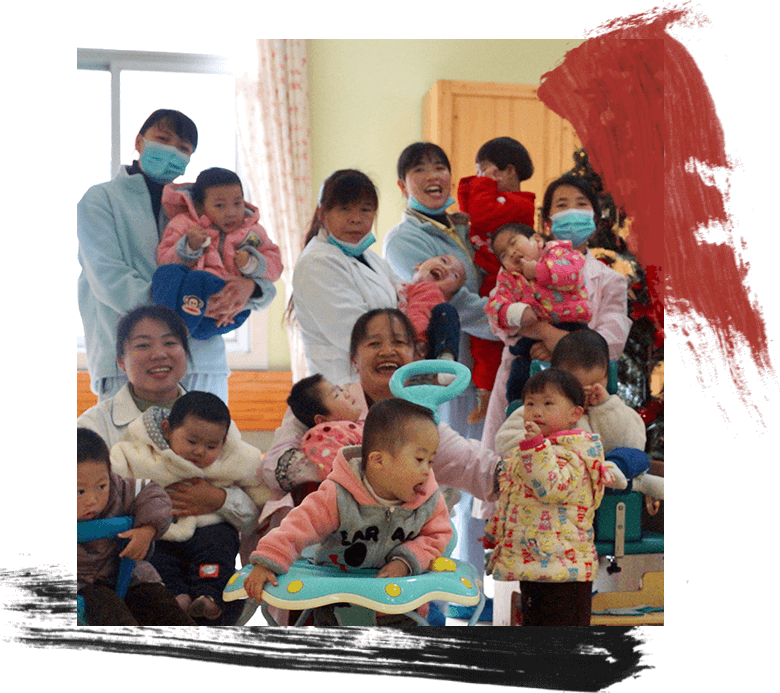 Many care workers holding young children all with happy faces.